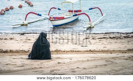 Muslim women in Abaya Niqab sitting and relaxing the beach at the sea. Local Boat in Background. Nusa Dua, Bali