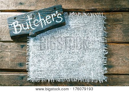 Vertical frame of white burlap on rough pine wood boards. Wooden tablet with text 'Butchers' as title bar. Structured natural style background