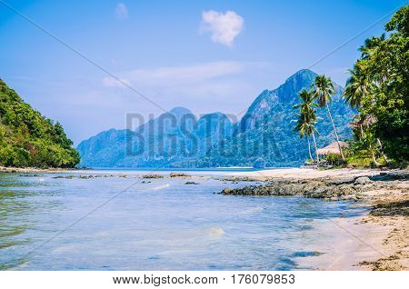Sunny Marimegmeg Beach in Low Tide in El Nido, Bar under Palms in Front, Palawan, Philippines