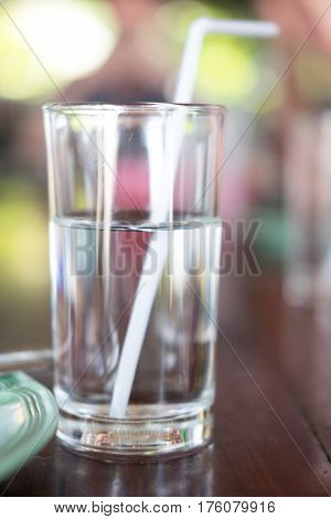 glass of water with straw on wood background