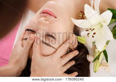 Facial beauty treatment at spa salon. Young woman relaxing while getting spa treatment. Beauty care