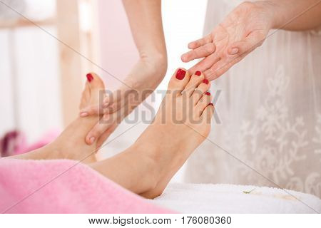 Close up of woman feet with red nailpolish getting relazing foot massage at spa salon