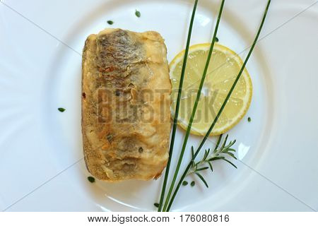 Top view of fried hake on the plate