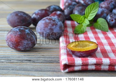 Close up of sweet plums and mint on woodentable