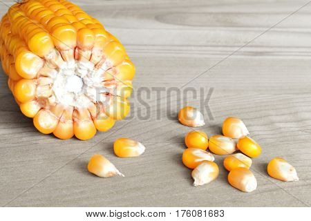 Corn cob and corn seeds on wooden background