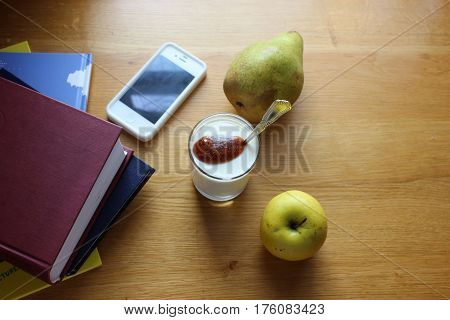 Table view with yogurt, fruits, smartphone and books. Stack of books, apple, pear, glass of yogurt an phone on wooden table. Snacks with stationery on wooden surface.