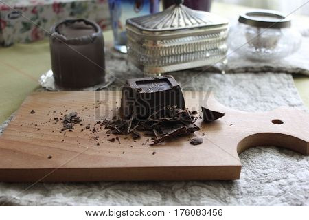 Cut into small pieces dark chocolate on wooden board. Table with chocolate on board with candle, silver sugar pot and glass vase on background.