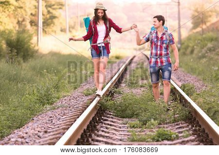 Young Couple Cute Girl and Handsome Boy walking along Railroad tenderly holding Hands and balancing on Rail
