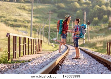 Man and Woman in travel style clothing with backpacks embracing and holding hands tenderly looking at each other on old country railroad with backlight sun