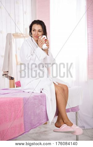 Young woman in white bathrobe and pink slippers having hot drink after massage. Body care