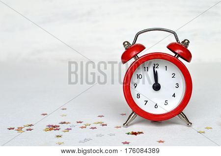 Happy New Year card with alarm clock striking midnight