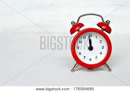 Red vintage alarm clock striking midnight or midday