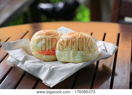 bread stuffed in paper napkin on a wooden table