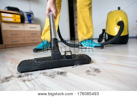 Person in professional uniform yellow pants blue shoes cleaning wooden floor with vacuum cleaner in home of modern office interior close up of cleaner brush