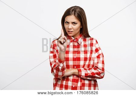 Portait of irritated woman shows stop sign with finger looking straight at camera with anger