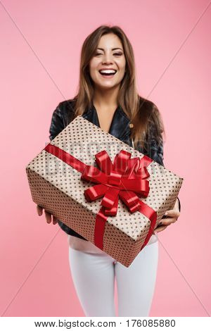 Smiling and happy young woman looks glad showing her big present box with red bow