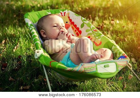 Peaceful baby in the rocking chair on the nature, on grass