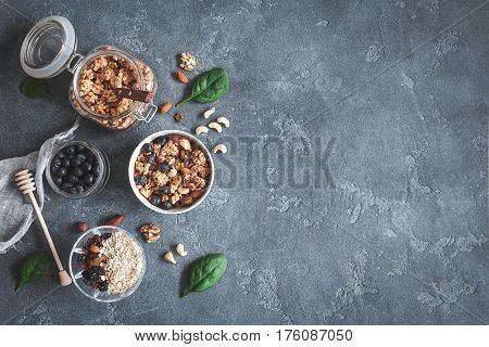 Healthy breakfast with muesli blueberry nuts on dark background. Flat lay top view