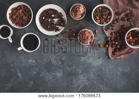 Cups of coffee chocolate cake chocolate muesli and chocolate ice cream on dark background. Flat lay top view copy space