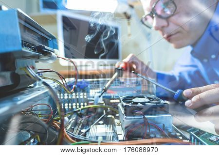 Throw the Window image of male Computer Technicians in blue uniform working with Hardware using tools including incandescent soldering iron with smoke in Service Workshop