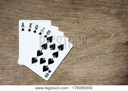Five card of black spade royal straight flush on wooden background