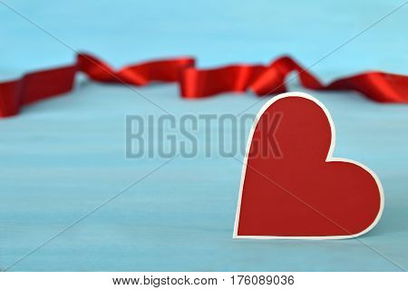 Valentine's Day heart and red ribbon on blue background