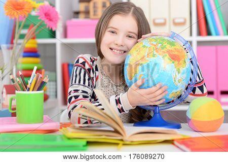 Portrait of a cute girl embracing a globe