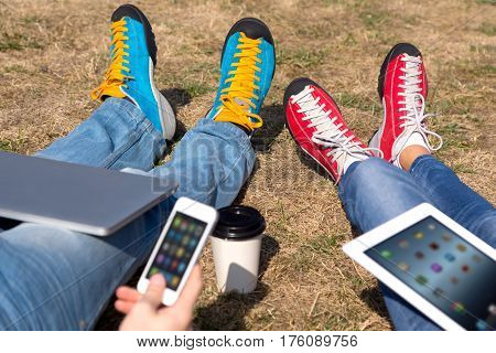 People relaxing on Meadow using electronic and communication Gadgets with focus on feet wearer in bright stylish sporty shoes