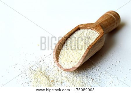 Semolina flour in scoop on light background