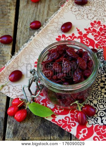 Dried Dogwood Cornelian Cherry Berry In Jar On Wooden Background. Selective Focus