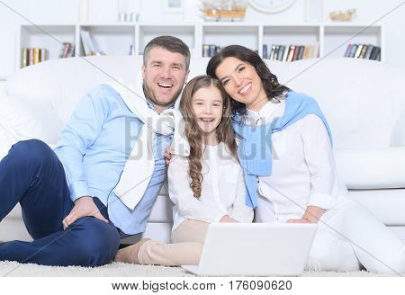 Portrait of a  family with daughter using laptop