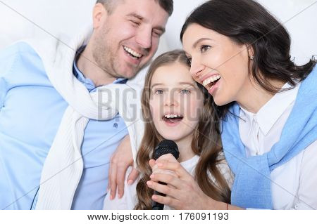 Portrait of a family with daughter singing karaoke
