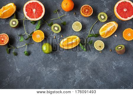 Colorful fresh fruit on dark background. Orange tangerine lime kiwi grapefruit. Fruit background. Summer food concept. Flat lay top view copy space