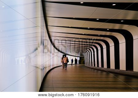 LONDON, UK - MAY 17, 2016: Commutes walking through futuristic looking pedestrian tunnel featuring an LED integrated light wall in Granary Square exit from Kings Cross Underground station.
