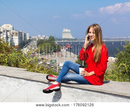 Young Woman talking on Telephone sitting on stone parapet in City downtown