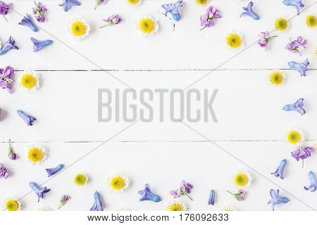 Flowers composition. Frame made of various colorful flowers on white wooden background. Flat lay top view