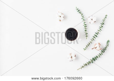 Workspace with cup of coffee cotton flowers eucalyptus branches. Flat lay top view