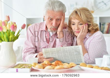 Portrait of an elderly couple having breakfast and reading a newspaper
