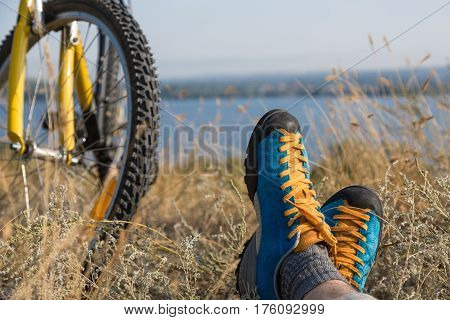 Bicyclist in bright sporty Shoes resting on yellow autumnal Grassy Lawn along with Bicycle Rural View on Background Sunny wea