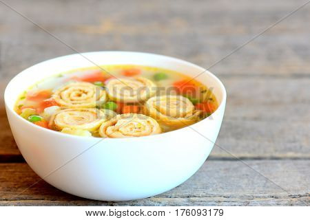 Light vegetable soup with omelet in a bowl isolated on rustic wooden background. Vegetarian soup with omelet, carrot, peas, leek, cauliflower and potatoes. Closeup