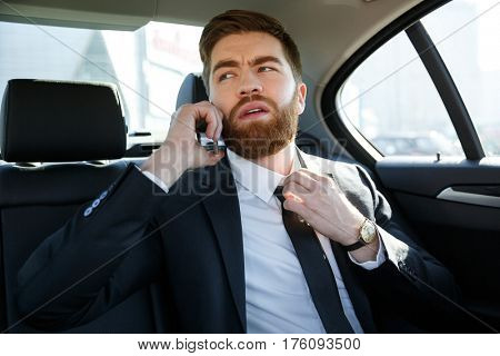 Handsome annoyed young business man talking on mobile phone and touching his necktie while sitting in back seat of a car