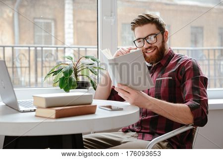 Photo of cheerful bearded young man student wearing glasses sitting in cafe while reading books. Looking at book.