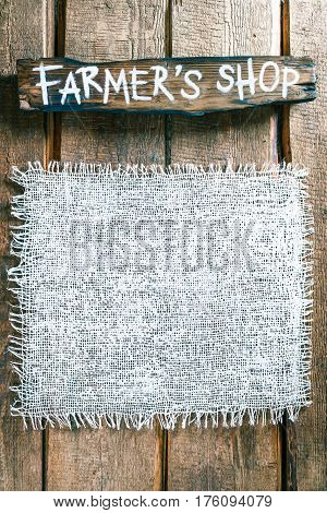 Vertical frame of white burlap on rough pine wood boards. Wooden tablet with text 'Farmers shop' as title bar. Structured natural style background