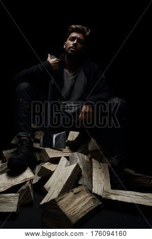 young beautiful man in studio shows an ax. seat on firewood