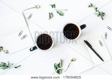 Workspace with notebook cups of coffee and rose flowers. Top view flat lay