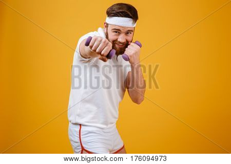 Smiling sportsman which beats at camera while holding lightweight dumbbells in hands. Isolated orange background