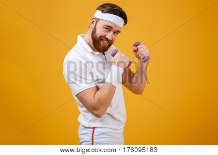 Sportsman which standing sideways while holding lightweight dumbbells in hands and looking at camera. Isolated orange background