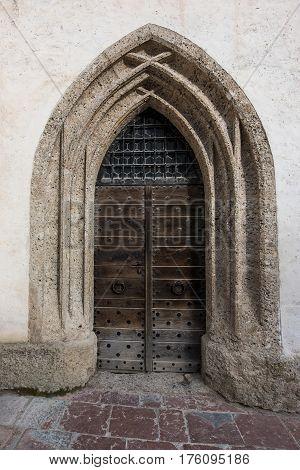 Ancient wooden door in stone arch in white stone building, Salzburg, Austria