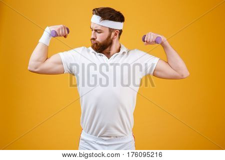 Serious retro sportsman which doing exercise with lightweight dumbbells and showing his biceps. Isolated orange background