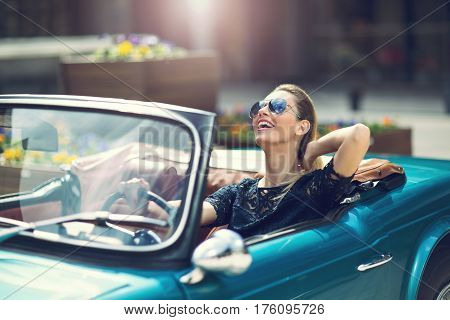 Portrait of beautiful sexy fashion woman model sitting in luxury retro cabriolet car